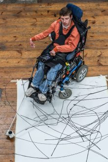 Charity PR photo of invention Enayball that has won a Blackwood Design Award for helping highly paralysed people make art independently. Picture shows man in wheenchair using device to draw on canvas.
