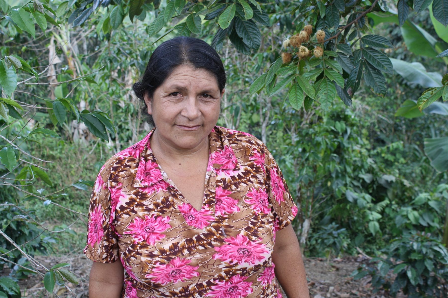 Edinburgh PR photo of worker Maria Eugenia Maldonado Ocana who works for Equal Exchange - the coffee supplier for Surgeons Quarter's Cafe 1505. She is wearing a pink shirt, has her hair tied back and is stood in front coffee plants