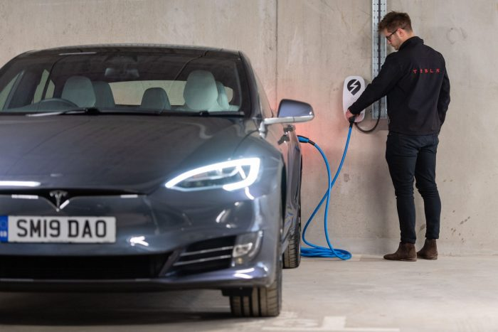 PR photography shows Tesla Sales Consultant 'plugging in' to EV charging provision at The Crescent at Donaldson's by CALA Homes (East)