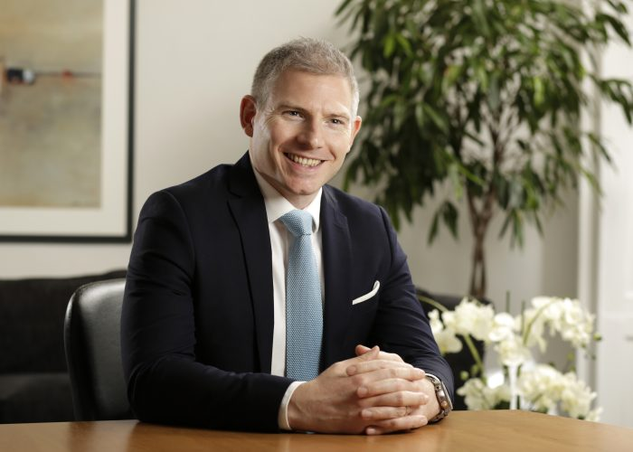 Andrew Inglis, Head of Legal at Core-Asset Consulting sitting at a desk