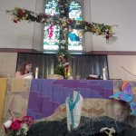 The fully flowered cross set up behind the altar.