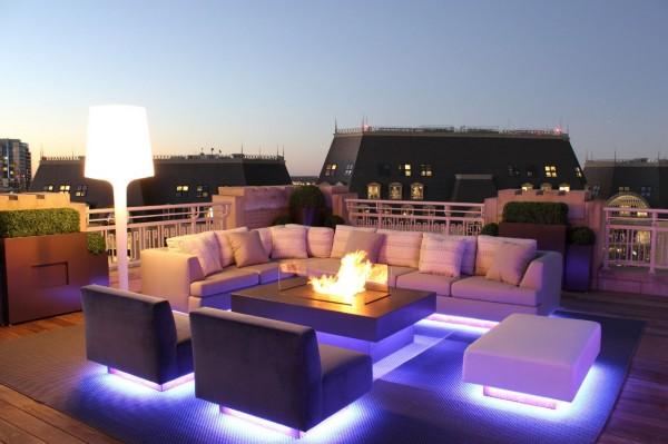 Mobiliário de exterior moderno parece flutuar sobre dramáticos up-lights.