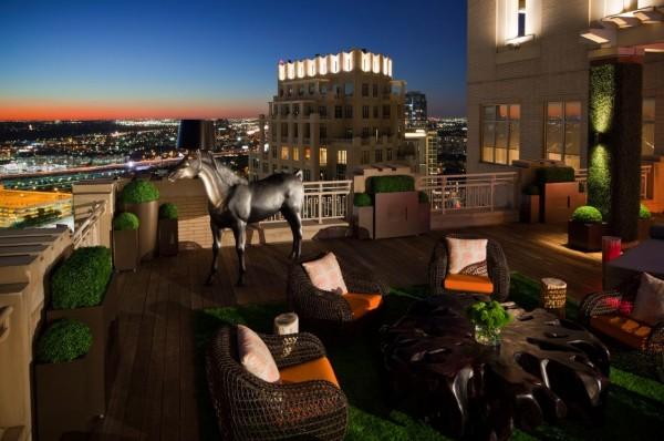 O horizonte da cidade situa-se no pano de fundo deste terraço conforto de espírito equipados com assentos contemporânea e elementos orgânicos.