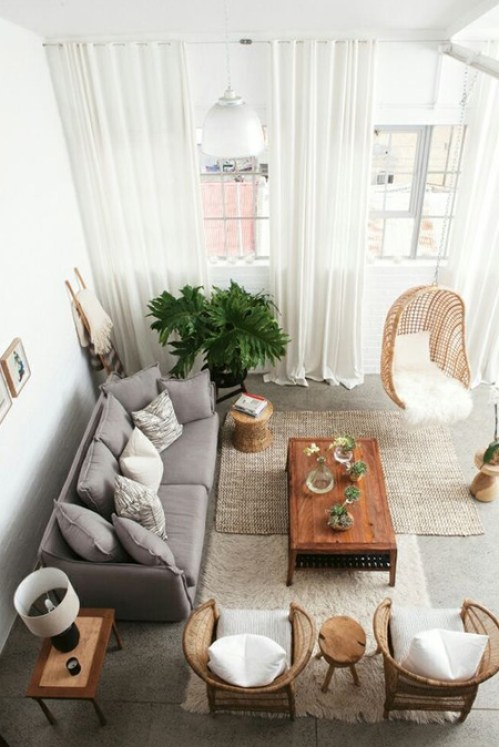 In this small living room, the curtains are mounted higher than the actual window size to draw the eye upwards and deflect from the small proportions of the space.