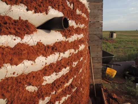 Then cob with straw is thrown at the wall, smoothed, and dabbled with finger-holes