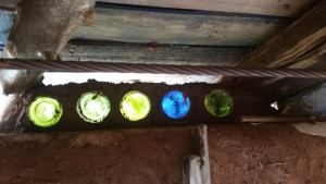 Above the wall, below the ceiling colored bottles