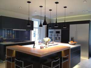 luxurious kitchen with black cabinets and pendant lights
