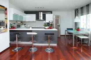 U-shaped contemporary kitchen with black and white bar stools