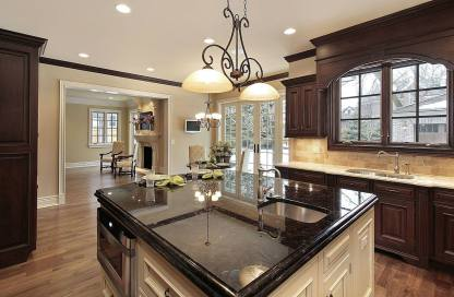modern cream kitchen with glossy black countertop in the island