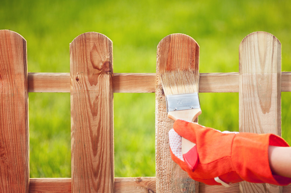 Protective sealant being applied to a wooden fence