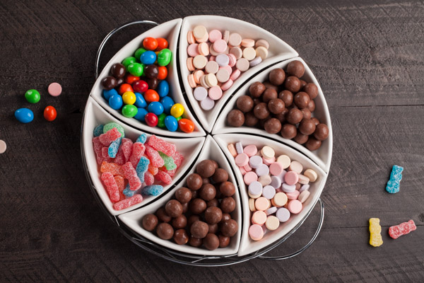 Movie candy assortment on a platter with chocolate covered peanuts, hard candy, and gummies