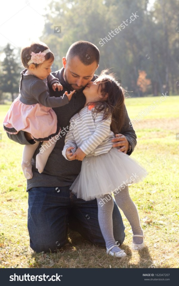 Hispanic father kissing and hugging his two girls - income report