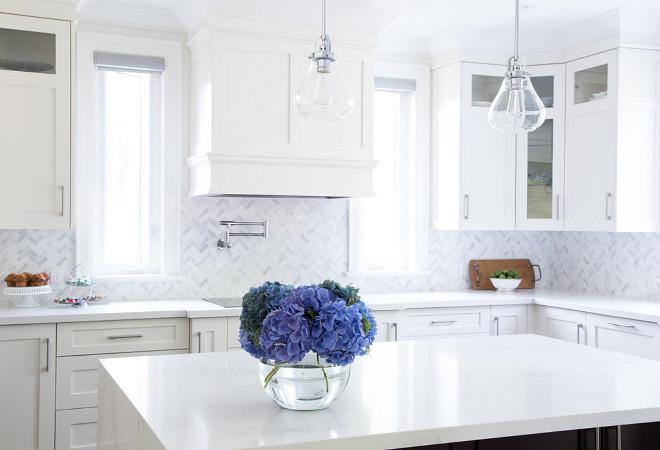 Crisp white kitchen painted in Benjamin Moore White Dove OC-17 and marble backsplash tile in herringbone pattern. barlow reid design