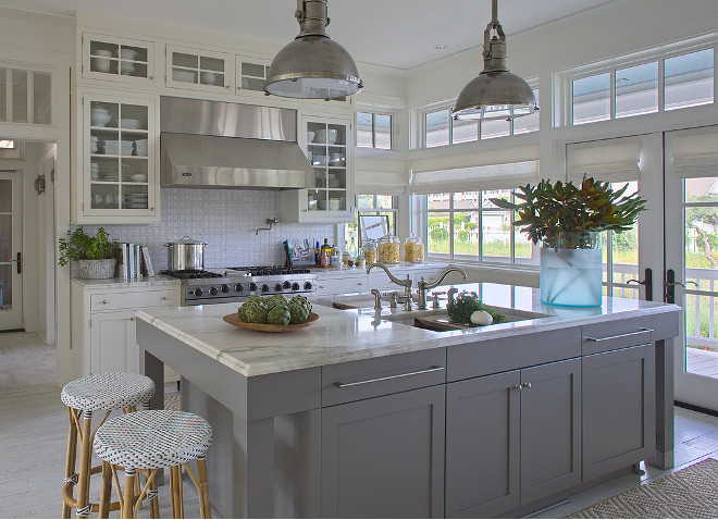 White kitchen with gray island. This white and gray kitchen features Chart House 1 Light Country Industrial Pendants in Antique Nickel with Large Antique Nickel Shades. The bistro barstools are Serena & Lily Riviera Backless Stools. The back of the kitchen boasts white glass-front cabinets surrounding a stainless steel kitchen hood over swing-arm pot filler over stainless steel stove beside windows and French doors under transom windows. White kitchen cabinet with gray island. White and gray kitchen #Whitekitchen #Grayisland #whiteandgraykitchen #whitecabinets #grayisland #kitchen Urban Grace Interiors.