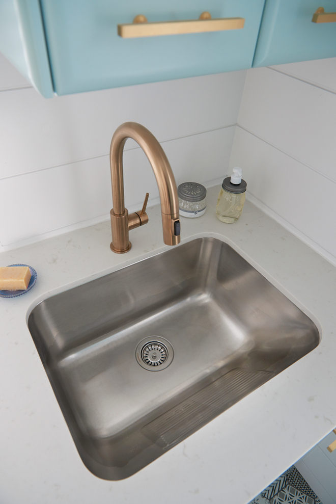 Well appointed contemporary laundry room boasts a curved stainless steel sink fixed to a white quartz countertop and paired with a gold gooseneck faucet mounted in front of a white shiplap trim beneath blue cabinets painted in Gossamer Blue by Benjamin Moore and finished with brass pulls. #laundryroom Soda Pop Design Inc.