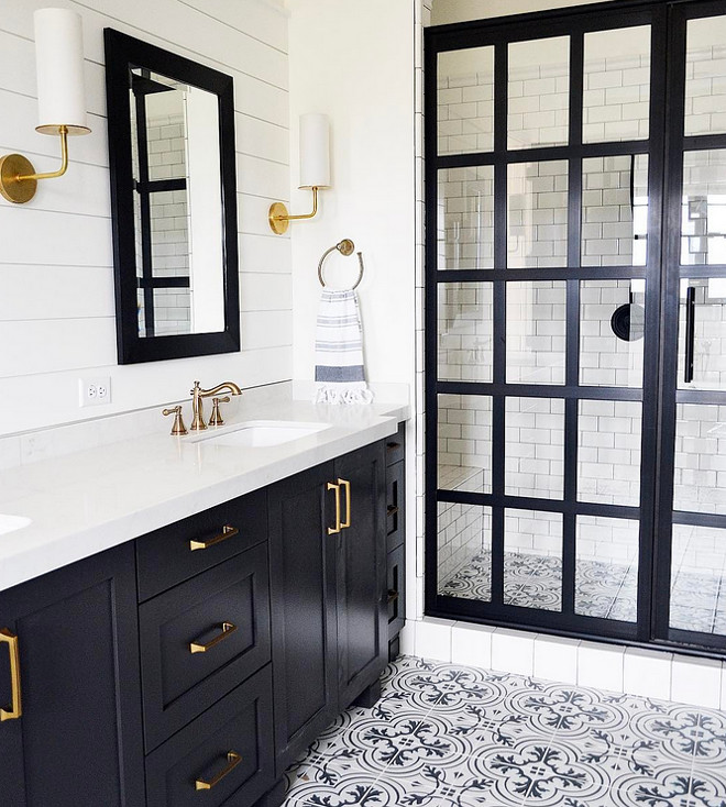 Modern Farmhouse Bathroom with black framed shower doors. Modern Farmhouse Bathroom with black framed shower door, black vanity, brass fixtures, shiplap paneled wall and cement floor tile. Shower screen door black metal and glass. #ModernFarmhouseBathroom #ModernFarmhousebathrooms #blackframedshowerdoors #blackshowerdoor #FarmhouseBathroom #blackframeshower #blackframeshowerdoor #shiplap #cementfloortile #cementtile