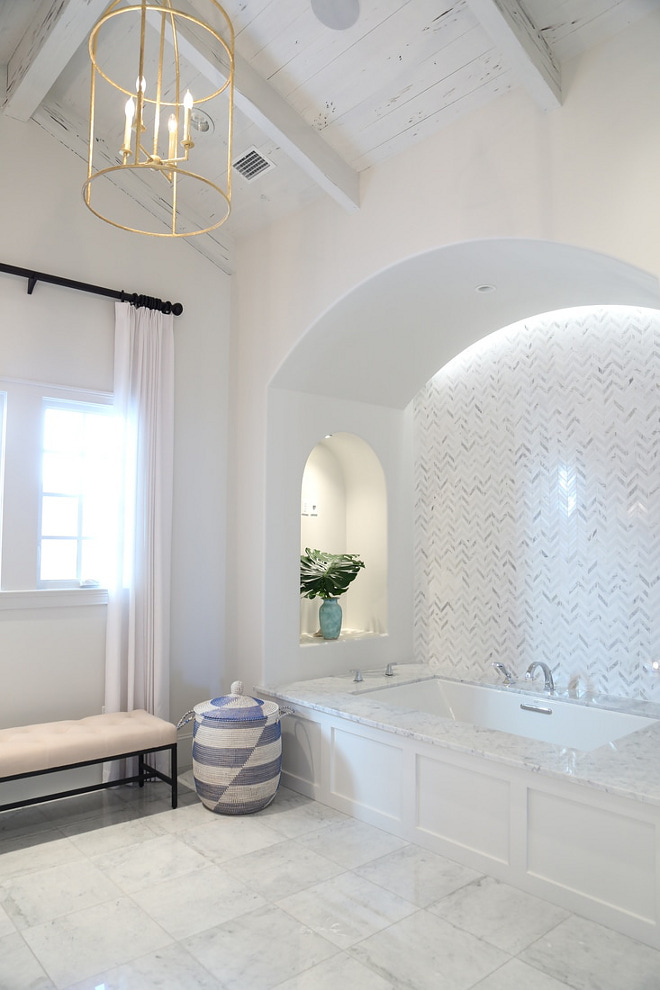 Tub Nook. Arched Bathtub Nook with marble herringbone backsplash tile. Ceiling features rustic Pecky Cypress Wood. Paint Color is Benjamin Moore White Dove. #TubNook #Bathnook #bathroom #ArchedBathtubNook #archednook #marbleherringbonebacksplashtile #herringbonebacksplashtile #Ceiling #rusticwoodceiling #PeckyCypress #Woodceiling #PaintColor #BenjaminMooreWhiteDove Old Seagrove Homes