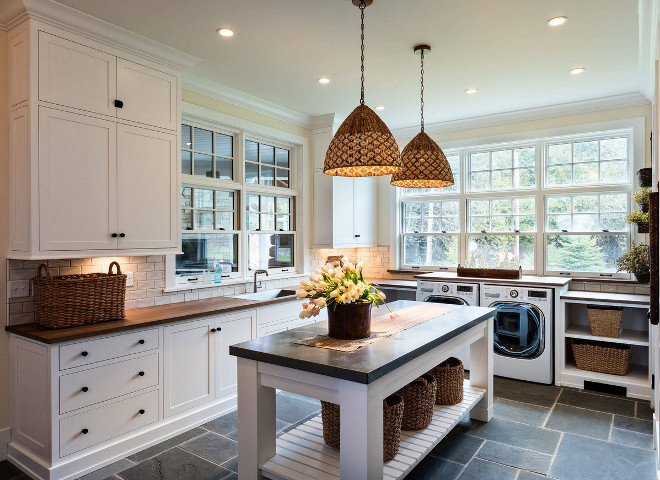 Laundry Room Inspiration Ideas. Laundry room with custom folding island, Blustone floor tile and woven pendants. Pendant lights are from Serena and Lily. #laundryroom #laundryroominspiration #laundryroomisland #foldingisland Mitch Wise Design,Inc.