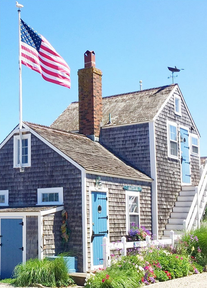 Nantucket Shingle Cottage with blue front door and blue shutters. Via glimpse guides