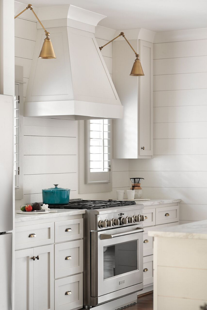 Shiplap kitchen. White kitchen with shiplap backsplash and shiplap walls with shaker style cabinet and brass lighting flanking hood. #kitchen #shiplap #backsplash #kitchenshiplap #shiplapkitchen #hood Willow Homes