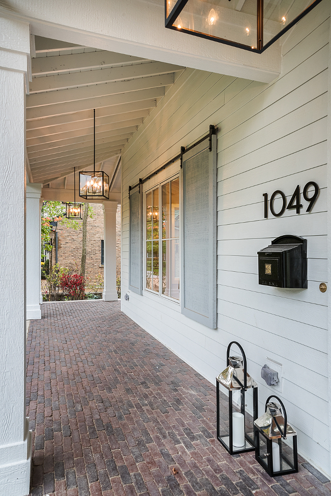Brick Porch. Long porch with brick floor tile and grey shutters with barn door hardware Brick Porch. Long porch with brick floor tile and grey shutters with barn door hardware #Brick #Porch #brickporch #brickfloortile #greyshutters #barndoorhardware