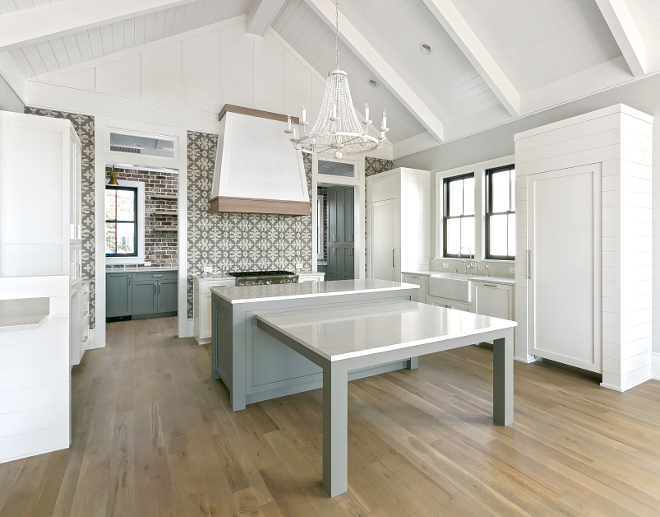 Transitional white and grey kitchen with vaulted shiplap ceiling, shiplap cabinet paneling, cement tile backsplash, white oak hardwood floors and kitchen island with attached table
