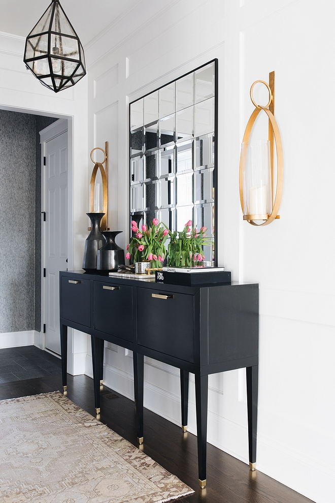 Foyer black console table This ebony console table brings personality and some contrast against the white paneling ebony console table back and white interiors