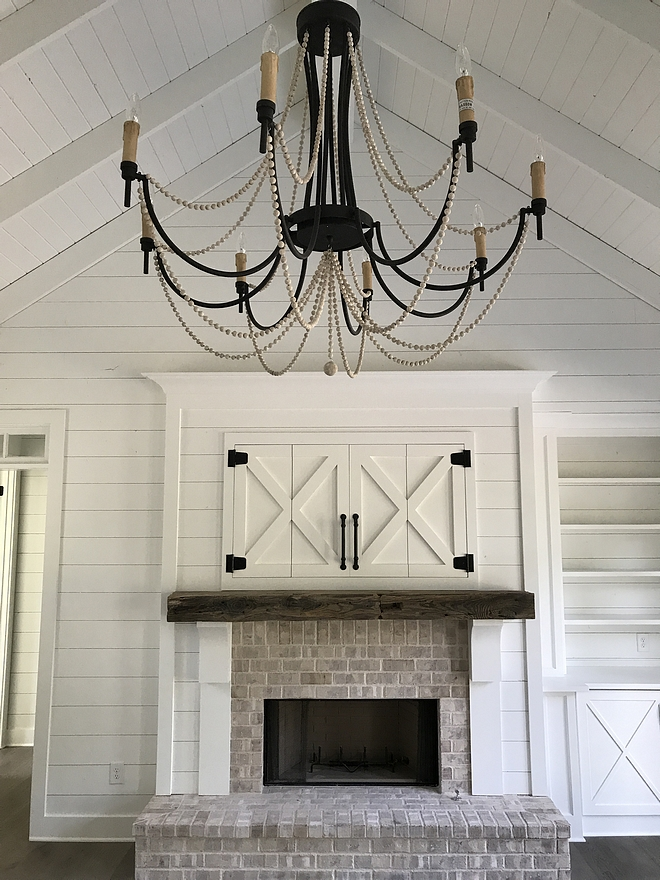 Fireplace Farmhouse Fireplace Brick Fireplace with Beam over Fireplace Antique Railroad Tie Shiplap and hidden TV with Barn style doors