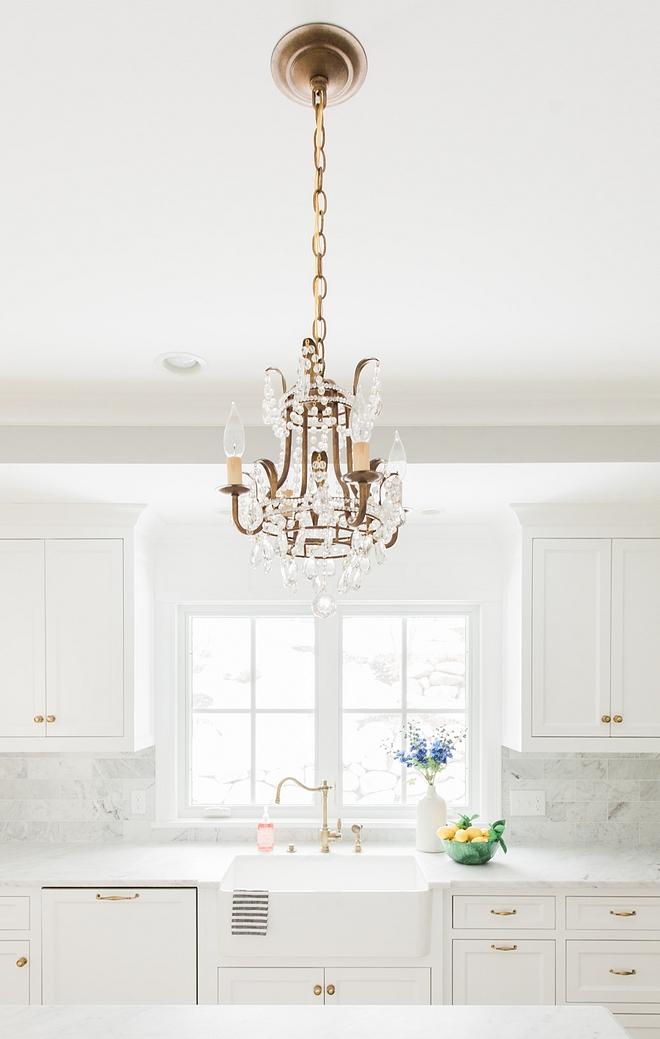 Kitchen Hardware Knobs and pulls Brass antigue English brass against white kitchen cabinets and antique brass chandelier over kitchen island