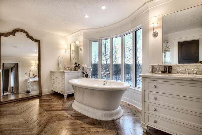 French Bathroom French Bathroom Design French Master Bathroom with paneled walls inset mirrors free standing tub and chevron hardwood flooring #Frenchbathroom #bathroom #chevronflooring