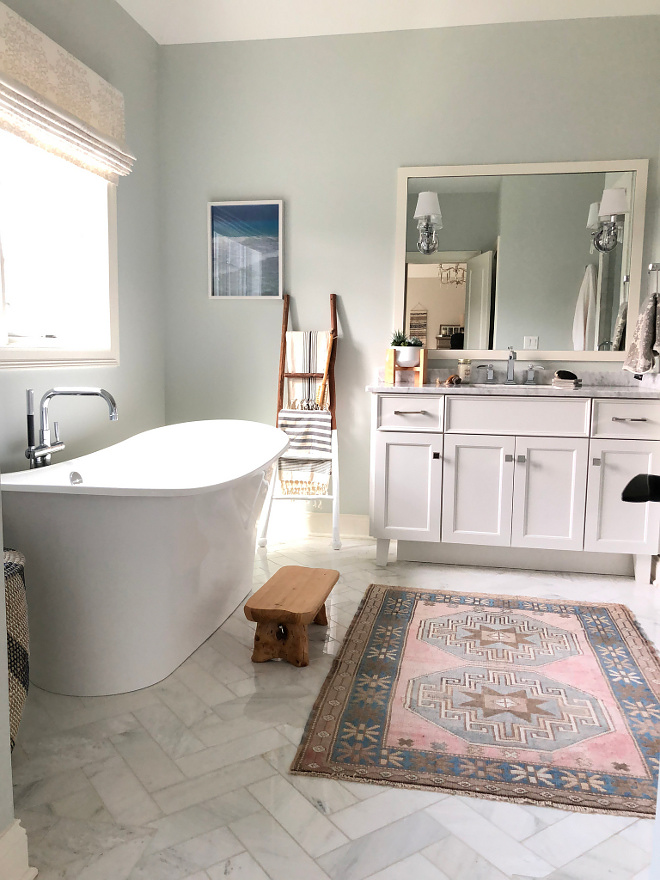 Bathroom with white marble herringbone floor tile soothing and blue grey walls All sources and paint colors on Home Bunch #bathroom #whitemarbleherringbone #herringnonetile #floortile
