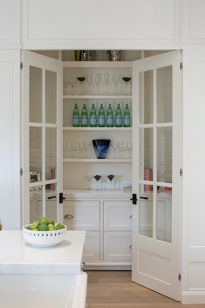 Pantry off kitchen with glass doors, open shelves, white marble countertop and lower cabinets with drawers Paint Color Benjamin Moore White Dove #Pantry #kitchenpantry #pantrydoors #PaintColor #BenjaminMooreWhiteDove