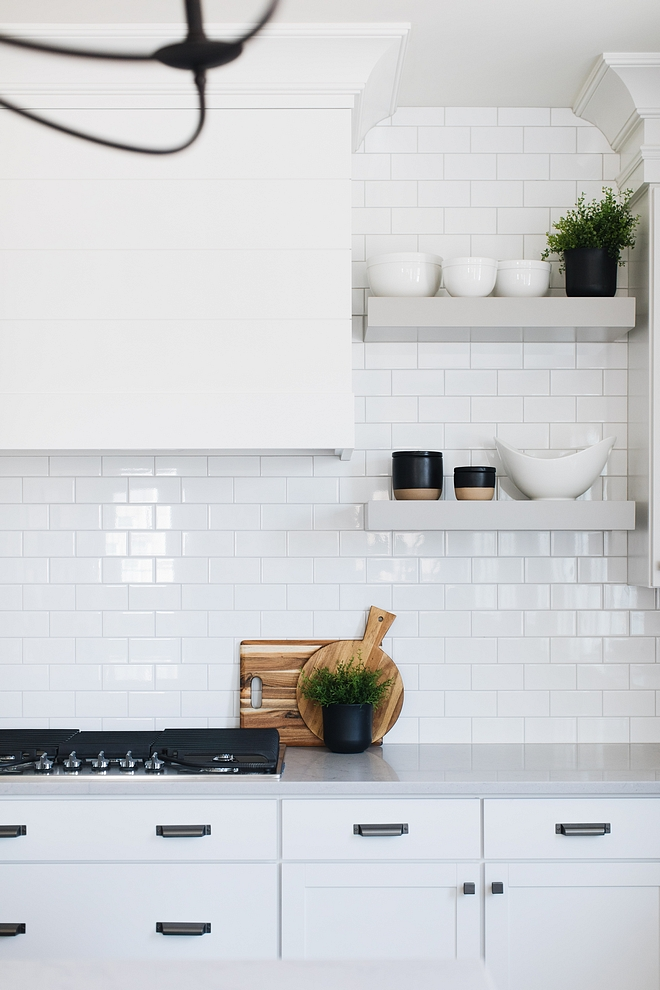 White kitchen with white subway tile backsplash and grey floating shelves to add contrast The grey floating shelves are painted in Ozark Shadows by Benjamin Moore #floatingshelves #kitchenfloatingshelves #OzarkShadowsBenjaminMoore