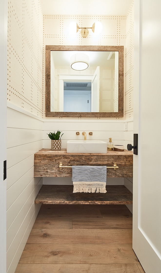 Farmhouse Farmhouse-style bathroom features half wall shiplap wainscoting with wallpaper above, wide plank hardwood flooring, reclaimed wood mirror, wall-mounted faucet, vessel sink and reclaimed wood freestanding vanity with shelf for baskets #farmhousebathroom #farmhouse #bathroom #shiplapwainscoting #reclaimedwood #freestandingvanity