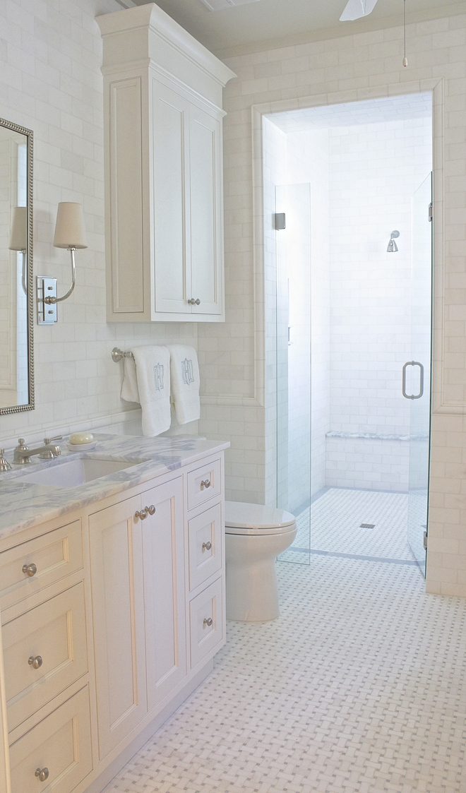 This bathroom features a classic combination of white subway tile on walls and marble basketweave floor tile Notice the curb-bless shower #bathroom #classicbathroom #curblessshower