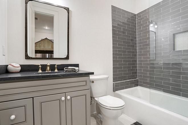 Boys bathroom with black countertop, grey vanity and charcoal grey subway tile