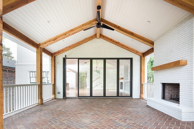 Farmhouse Outdoor Living Area This covered outdoor living space features vaulted ceiling with tongue and groove and beams, painted brick fireplace and brick flooring in a herringbone pattern #farmhouse #outdoorfarmhouse #paintedbrick #tongueandgroove #brick #herringbonebrick