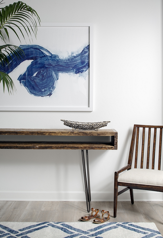 Foyer with midcentury console table with wood top and metal base, abstract artwork, blue and white rug and modern newel accent chair #foyer #midcentury #art #furniture #chair #rug