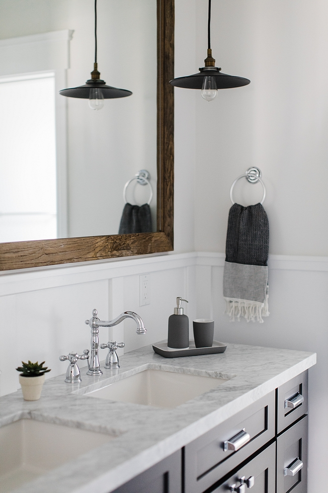 Bathroom features a dark charcoal cabinet with white marble top, double sinks and a large barnwood mirror Sources on Home Bunch #bathroom