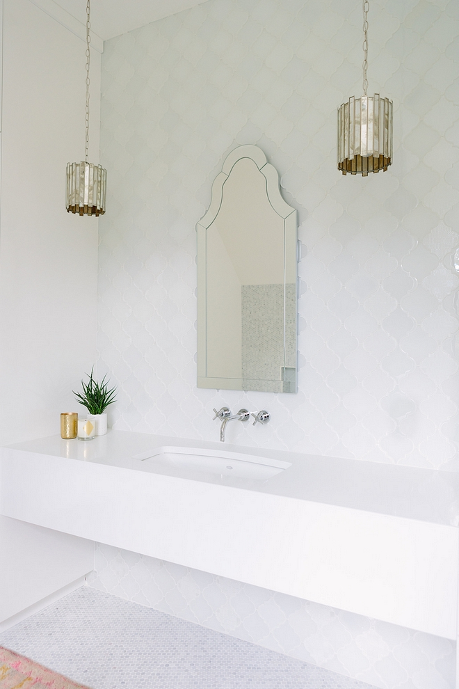 Bathroom with long floating vanity with white quartz countertop antique mirrored pendant lights and Arched Mirror #bathroom #floatingvanity #whitequartz #antiquemirrorpendants #ArchedMirror