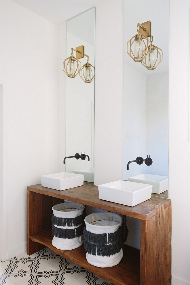 Transitional bathroom features a custom wooden console table used as vanity, vessel sinks and a pair of Moroccan embellished hampers Console table is better if made of solid hardwood - it would make a great DIY #transitionalbathroom #bathroom #vesselsink #Moroccanhamper