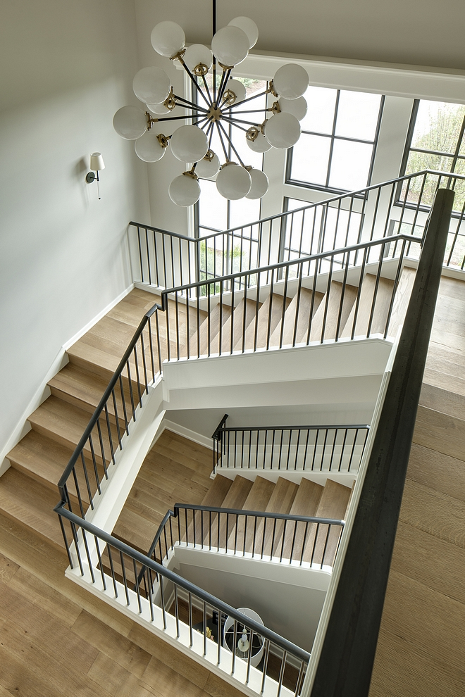 This gorgeous staircase features White Oak wood treads and wood risers. The metal railing is custom.  Window sashes Sherwin Williams Medium Bronze #staircase #whiteoak #metalrailing