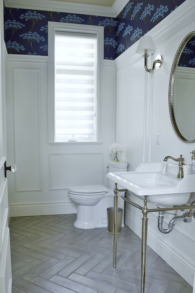 Powder Bathroom with Tall wainscoting and herringbone floor tile The classic herringbone tile design is always in style and effortlessly adds a trendy touch to the floor #PowderBathroom #bathroom #wainscoting #herringbone #floortile