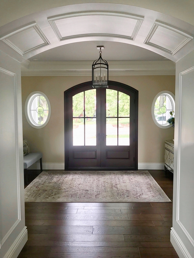Double door foyer with oval windows flanking front door Front door opens to a foyer with arched doorway leading to the main rooms #foyer #archeddoor #frontdoor #ovalwindows #archeddoorway