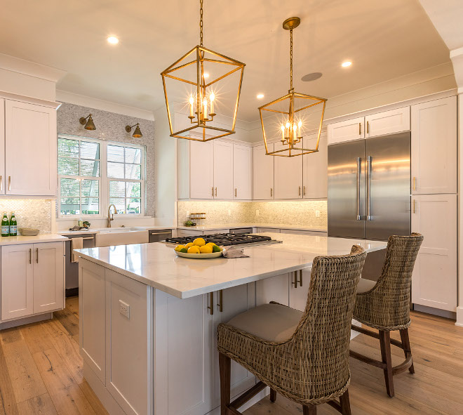 Kitchen Island with marble-looking countertop, hardwood flooring, stainless steel appliances and brass pendant lighting #kitchen #kitchenisland #brasspendantlighting #hardwoodflooring #marblelookingquartz #countertop