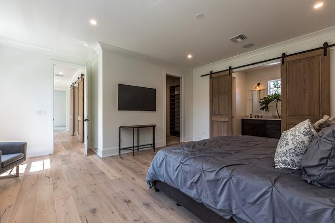 Modern farmhouse master bedroom with barn door to master bathroom