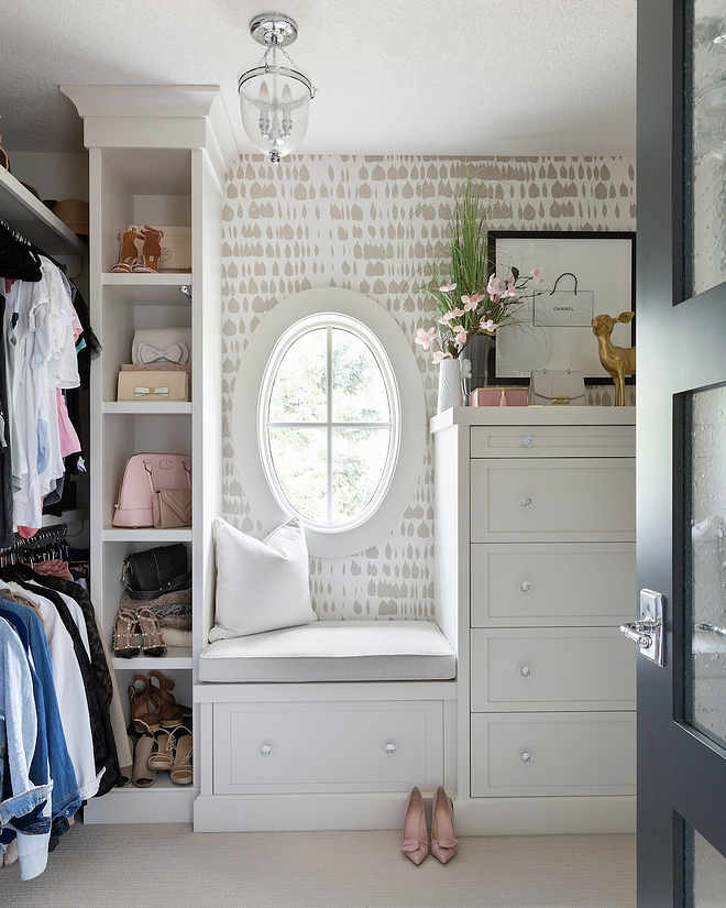 Her Closet The closet has lots of built-in shelving and a full dresser with jewelry drawers The oval shaped window lets in plenty natural light, which helps this space feel clean and airy #closet #hercloset #walkincloset #dressingroom
