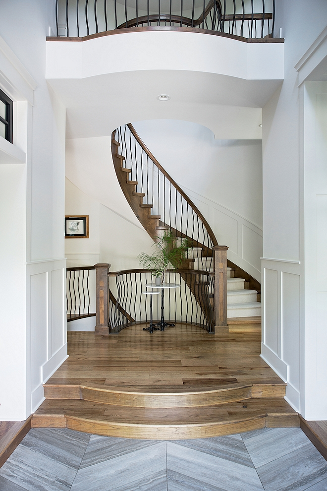 Foyer with grey Limestone in a chevron pattern and elevated hardwood flooring leading to a spiral staircase #foyer #chevronflooring #hardwoodflooring #spiralstaircase