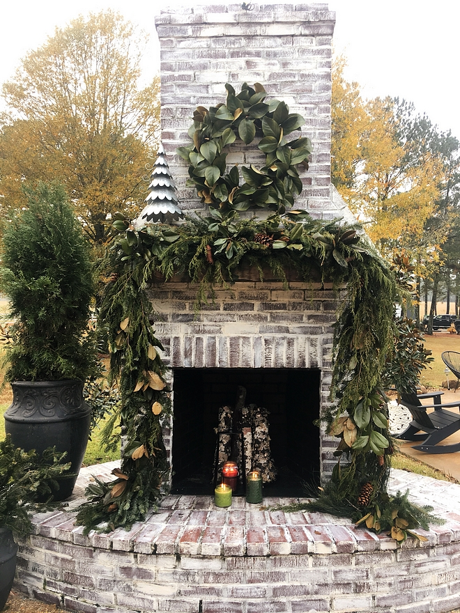 Whitewashed Brick Fireplace Outdoor Whitewashed Brick Fireplace decorated for Christmas with Magnolia Wreath and Magnolia and Fir garland #Fireplace #whitewashedbrick #whitewashedbrickfireplace #outdoorfireplace #Christmas