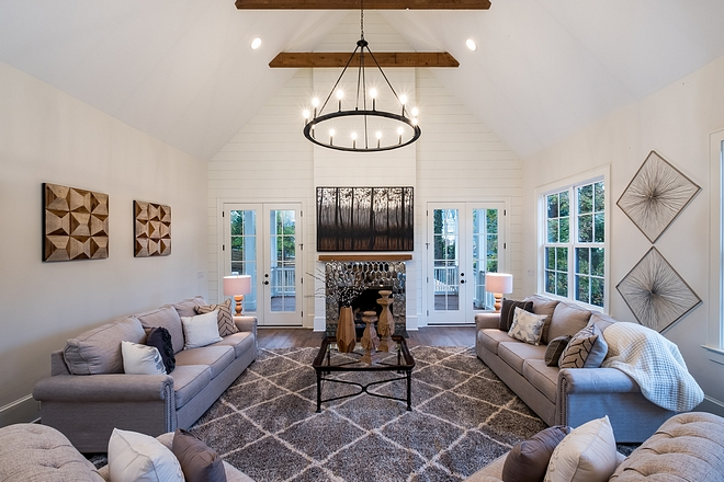 Farmhouse vibes start to really kick in With a full height shiplap accent wall it's hard to not just sit back, relax, and take it all in. Cedar exposed beams and a matching fireplace mantle help evoke a rustic feel The ceiling vaults to a grand scale of 20 feet, and that vault even continues outside to the covered porch